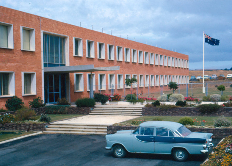 A brick building with a flag and old car in front